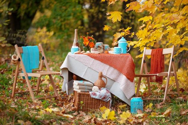 Tavola preparata per pranzo in natura autunnale, picnic.