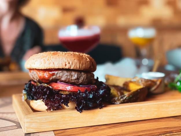 Sul tavolo del ristorante un hamburger con una cotoletta di vitello un anello di cipolla rossa basilico un pomodoro e