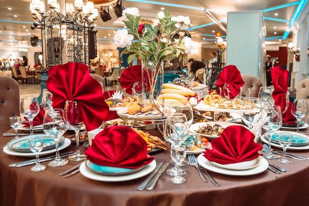 Un tavolo in un ristorante con cibo e tovaglioli rossi.