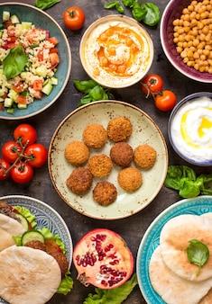 Tavola servita con piatti della tradizione mediorientale. ciotola con falafel, doner kebap, hummus