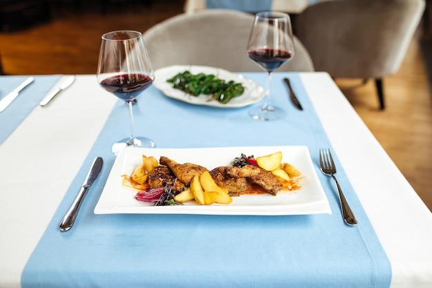 Tavolo servito con pollo arrosto con patate e peperoni padron spagnoli con vino rosso