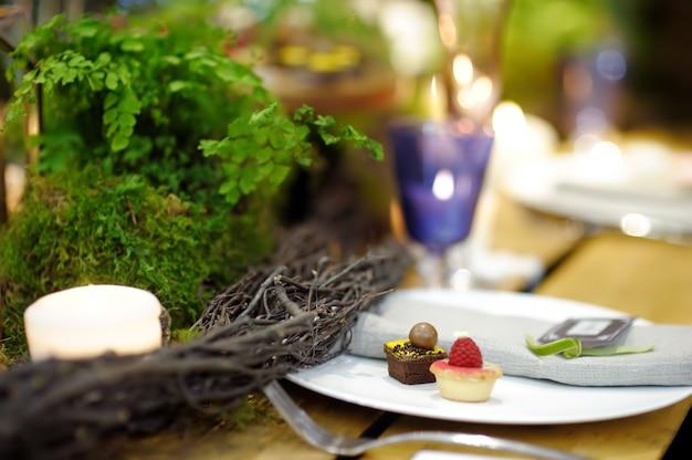 Tavolo apparecchiato per una festa o un ricevimento di matrimonio in stile rustico o scandinavo decorato muschio e felce. set da tavola alla moda.