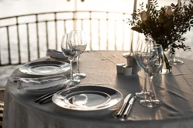 Tavola apparecchiata al ristorante sulla luce per un matrimonio, una cena romantica o una celebrazione