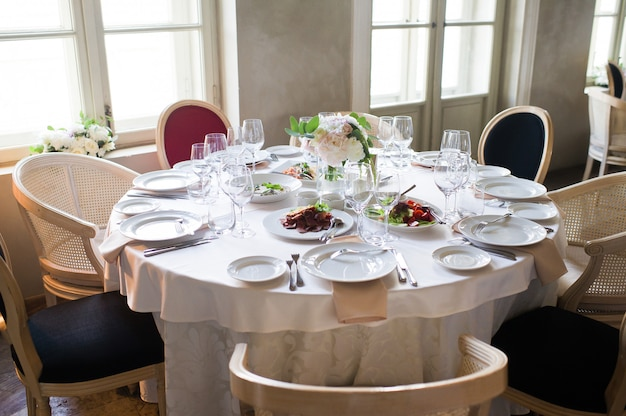 Tavolo apparecchiato al banchetto nuziale nel ristorante, stile classico con tovaglie e tovaglioli bianchi, vasi con fiori.