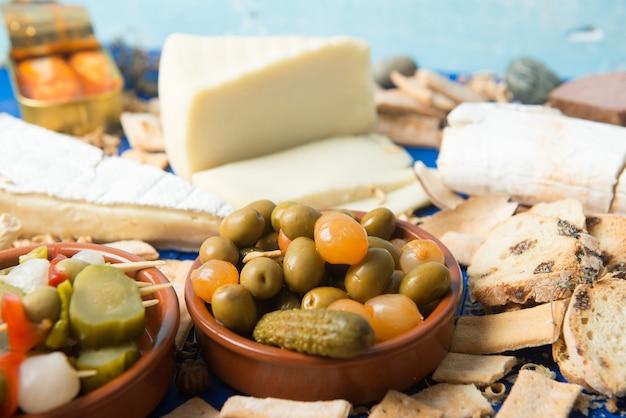 Tavola apparecchiata con aperitivo composto da cibi diversi formaggi e lattine di sottaceti