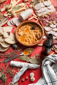 Tavola apparecchiata con uno stufato di fagioli asturiani dalla spagna e diversi antipasti con salsicce