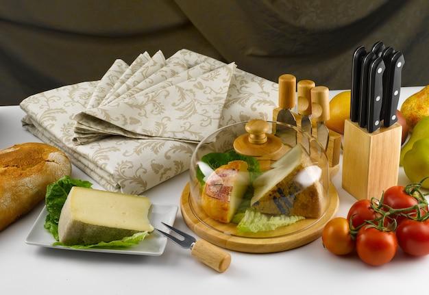Set da tavola con coltelli da formaggio e molti diversi tipi di formaggio