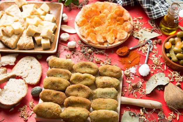 Tavola apparecchiata con una porzione di polpo galiziano dalla spagna e diversi antipasti con salsicce