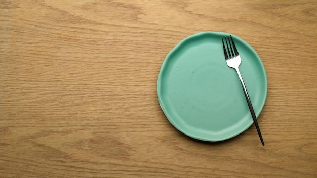 Impostazione tabella sfondo, mock up piatto in ceramica, forchetta e copia spazio sul tavolo di legno, vista dall'alto