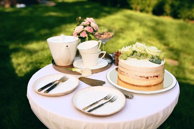 Regolazione della tabella, teiera in ceramica, tazze da tè, torta e fiori closeup, nessuno. argenteria di lusso su tovaglia bianca, stoviglie all'aperto
