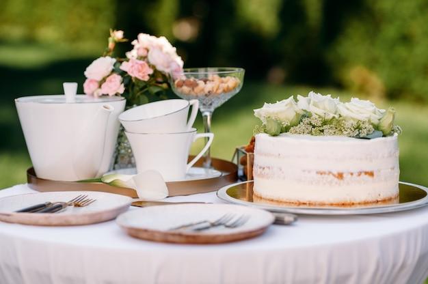 Regolazione della tabella, teiera in ceramica, tazze da tè, torta e fiori in primo piano, vista laterale, nessuno. argenteria di lusso su tovaglia bianca, stoviglie all'aperto