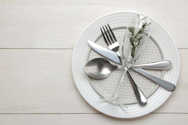 Regolazione della tavola. posate. forchetta, coltello, bicchiere, cucchiaio e piatto su un tavolo di legno bianco. vista dall'alto
