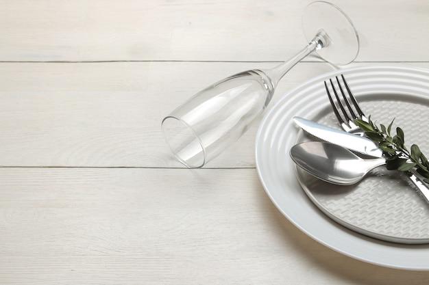 Regolazione della tavola. posate. forchetta, coltello, bicchiere, cucchiaio e piatto su un tavolo di legno bianco.