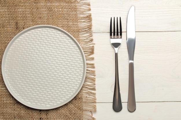 Regolazione della tavola. posate. forchetta, coltello e piatto grigio su un tavolo di legno bianco. vista dall'alto