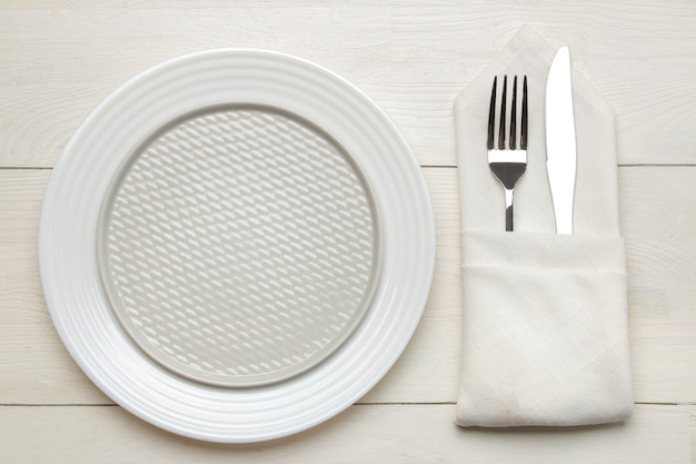 Regolazione della tavola. posate. forchetta, coltello in un tovagliolo e un piatto su un tavolo di legno bianco. vista dall'alto