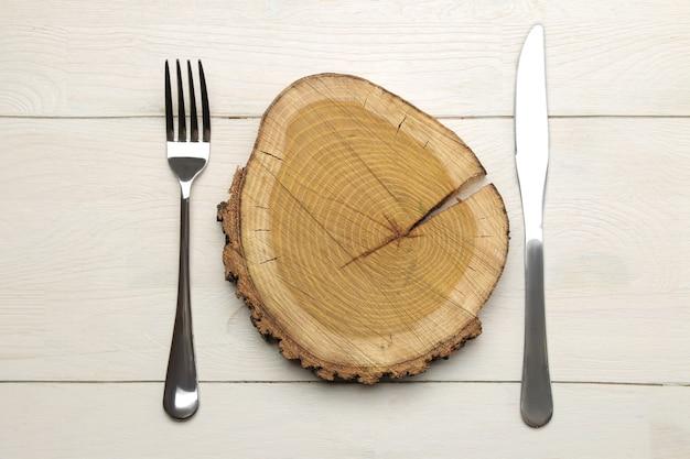 Regolazione della tavola. posate. forchetta, coltello e supporto in legno su un tavolo di legno bianco. vista dall'alto