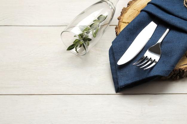 Regolazione della tavola. posate. bicchiere da vino forchetta, coltello in un tovagliolo blu e un supporto in legno su un tavolo di legno bianco.
