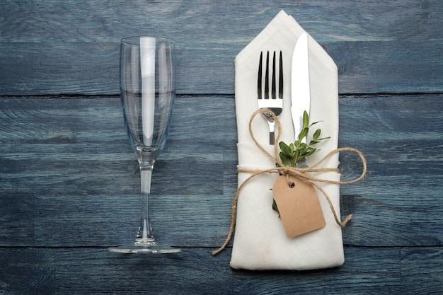 Regolazione della tavola. posate. bicchiere di vino forchetta, coltello in un tovagliolo bianco su un tavolo di legno blu. vista dall'alto