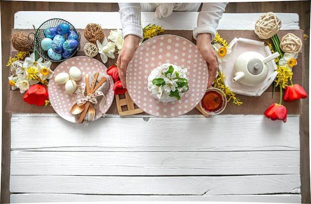 Impostazione della tavola per le vacanze di pasqua. tè, torte fatte in casa, uova e fiori su un tavolo di legno.