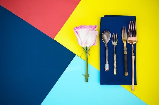 Regolazione della tavola, fiore e argenteria sul primo piano blu del tovagliolo, vista superiore, nessuno. decorazione per banchetti, tovaglia colorata, stoviglie