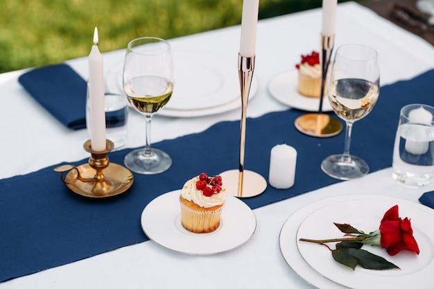 Regolazione della tavola, bicchieri, candele, fiori e dolci sul primo piano dei piatti, nessuno. argenteria di lusso e tovaglia bianca, stoviglie all'aperto