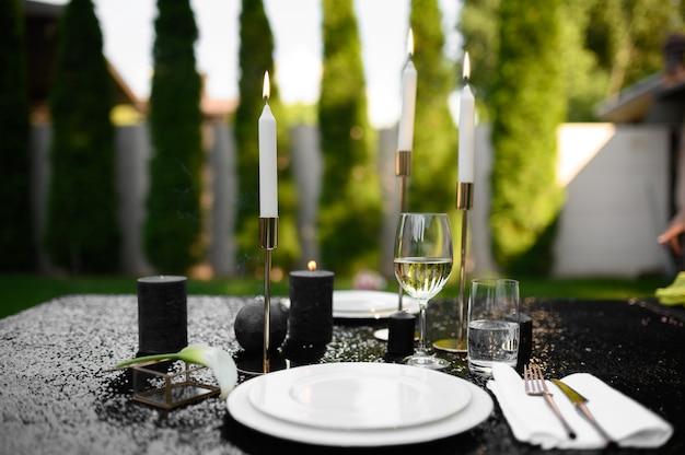 Regolazione della tavola, bicchieri, candele e piatto sulla parte superiore nera, nessuno. argenteria di lusso, articoli per la tavola all'aperto, decorazioni eleganti. festa romantica sul prato estivo