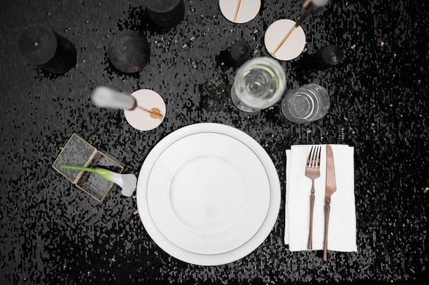 Regolazione della tavola, bicchieri, candele e piatto su nero, vista dall'alto, nessuno. argenteria di lusso, articoli per la tavola all'aperto, decorazioni eleganti. festa romantica sul prato estivo