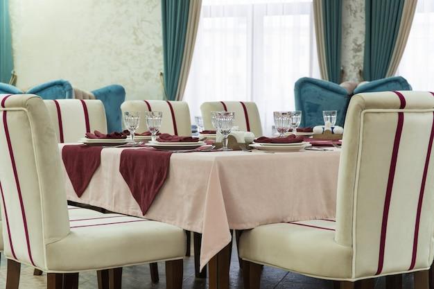 Regolazione della tavola in un ristorante lussuoso sullo sfondo della finestra
