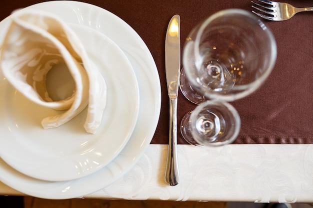 Regolazione della tavola in un ristorante. bicchiere, piatto, forchetta, coltello