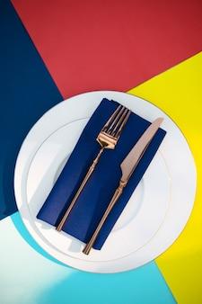Regolazione della tavola, posate sul primo piano del piatto, vista dall'alto, nessuno. decorazione per banchetti, tovaglia colorata e tovagliolo blu, stoviglie all'aperto