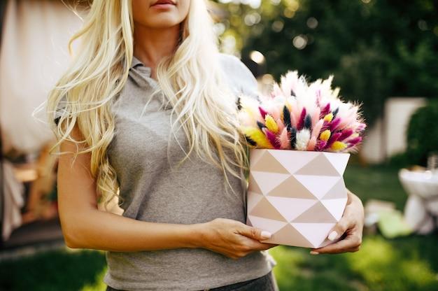 Regolazione della tavola, decorazione del tea party, la donna tiene il cesto con fiori di campo. stoviglie di lusso, ristorante all'aperto.