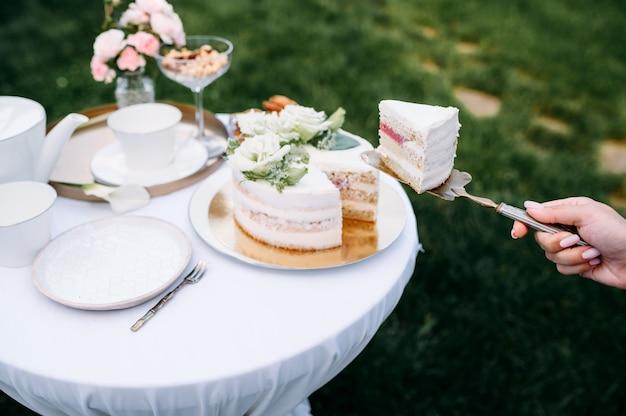 Regolazione della tavola, tea party, mano femminile prende il primo piano della torta, vista laterale. argenteria di lusso su tovaglia bianca, stoviglie all'aperto