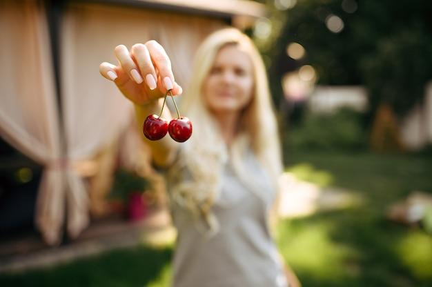 Impostazione della tavola, tea party, la donna mostra le ciliegie. stoviglie di lusso, ristorante all'aperto.