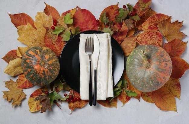 Impostazione della tabella il giorno del ringraziamento con zucca e foglie colorate con piatto al centro sulla superficie grigia. vista dall'alto