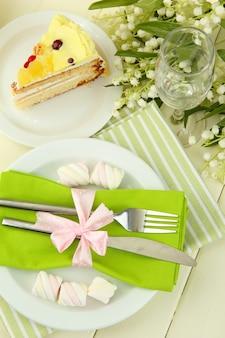 Apparecchiature da tavola nei toni del bianco e del verde su colore legno