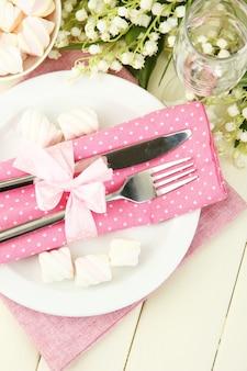 Impostazione della tavola nei toni del bianco e del rosa su superficie in legno colorato wooden