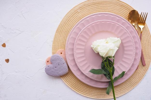 Apparecchiare la tavola. tovagliolo di vimini, due piatti rosa