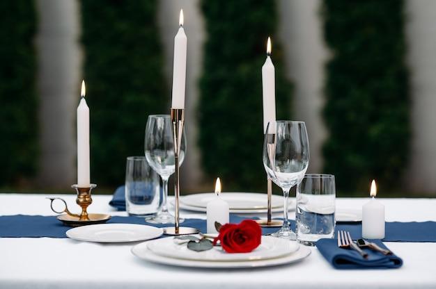 Regolazione della tavola, bicchieri di vino, candele e fiore sul primo piano del piatto, nessuno. argenteria di lusso e tovaglia bianca, stoviglie all'aperto