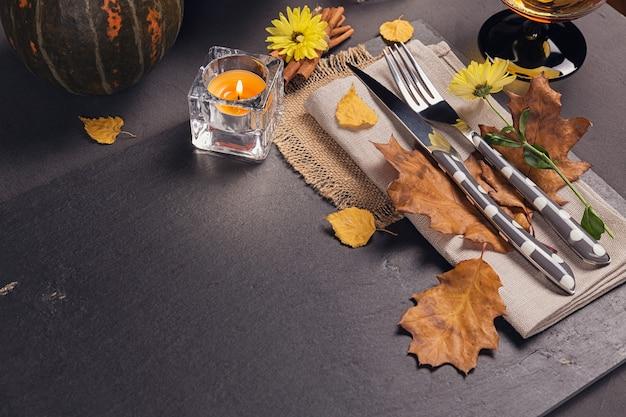 Apparecchiare la tavola con decorazioni autunnali per il ringraziamento. foglie secche con posate e bicchiere. sfondo autunnale del ringraziamento