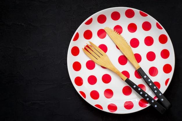 Regolazione della tavola con un coltello, una forchetta e un piatto di bambù con i pois su un fondo scuro