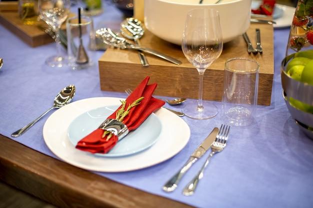 Apparecchiare la tavola con una tovaglia blu, un piatto bianco e blu, un tovagliolo rosso in un supporto d'acciaio con un ramo di rosmarino, elettrodomestici in acciaio, calici di vetro. primo piano, messa a fuoco morbida