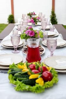 Regolazione della tabella con bicchieri di vino, posate e piatti