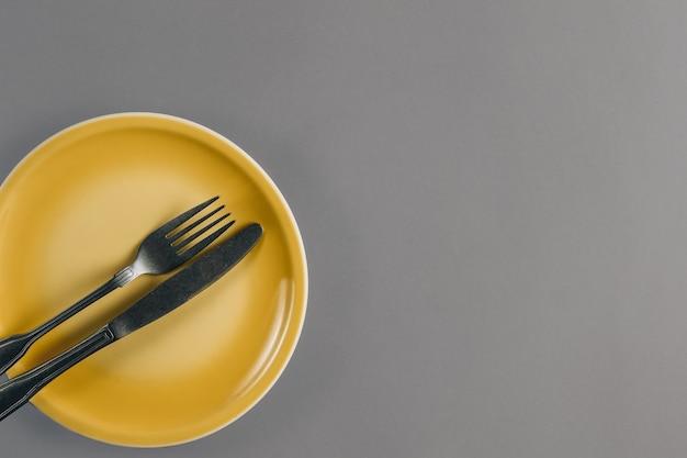 Regolazione della tabella - piatto giallo e posate sul tavolo grigio