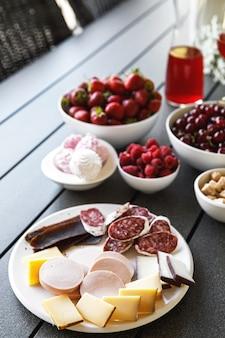Il tavolo sulla terrazza estiva è pieno di snack. formaggio, salsiccia, salame, carne e frutti di bosco.