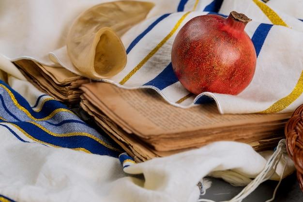 Sul tavolo della sinagoga sono i simboli di rosh hashanah mela e melograno, shofar talith