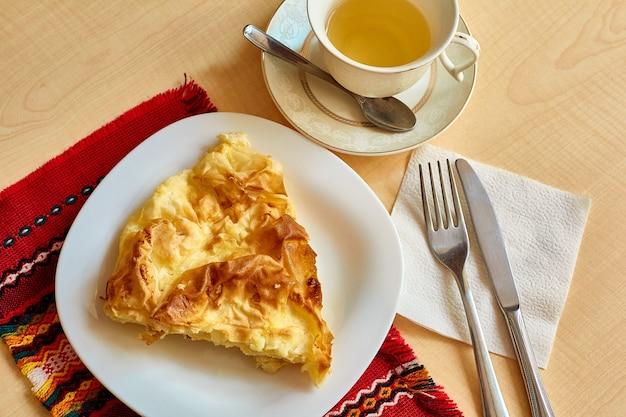 Sul tavolo c'è una frittata in un piatto, una tazza di tè con un piattino e un cucchiaino, un coltello e una forchetta su un tovagliolo