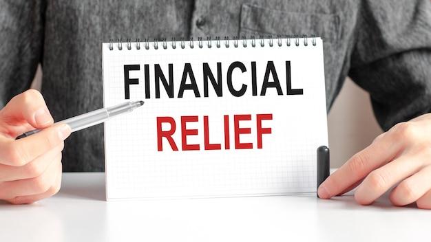 Sul tavolo c'è un pennarello rosso e una tavoletta di carta bianca su cui è scritto il testo: sollievo finanziario, lettere rosse e nere. concetto di affari.