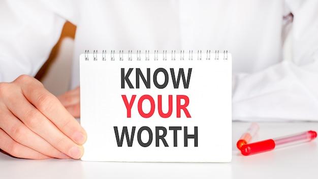 Sul tavolo c'è un pennarello rosso e una tavoletta di carta bianca su cui è scritto il testo: conosci il tuo valore, lettere rosse e nere. concetto di affari.