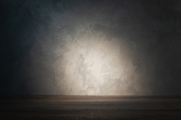 Piano del tavolo sul muro di cemento con raggio di luce