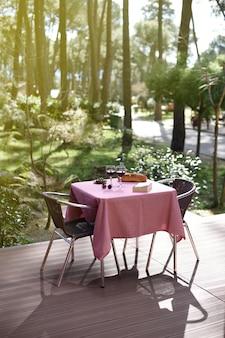 Tavolo per due con bicchieri da vino in un ambiente naturale all'aperto concetto covidsecure